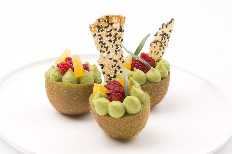 Kiwi gevuld met zoete avocadomousse, sinaasappel, framboos en sesamkletskop